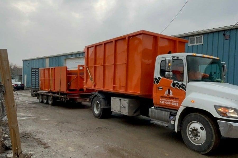 Image depicts the Bins Toronto truck hauling disposal rental bins