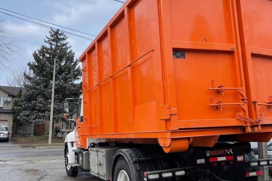 Image depicts an orange rental disposal bin from Bins Toronto